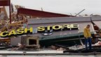 A business owner stands in front of a collapsed shop front on the main street in Harrisburg, Illinois after a storm with tornadoes ripped through the town in the early hours of Wednesday morning 29 February 2012