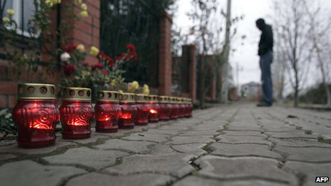 Candles burn outside the house in Krasnodar, southern Russia, where 12 people were massacred. Image from November 2010