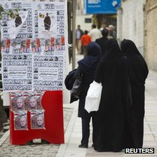 Women look at electoral posters in Tehran