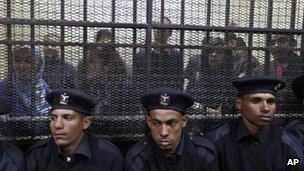 Egyptian policemen sit in front of Egyptian employees of several pro-democracy groups in Cairo, Egypt. 26 February 2012