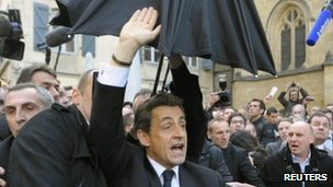 Nicolas Sarkozy is escorted by plain-clothes police out of Bayonne