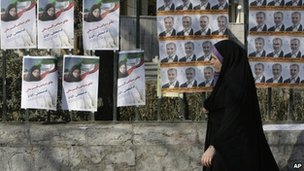 A woman walks past election posters in Tehran (28 February 2012)