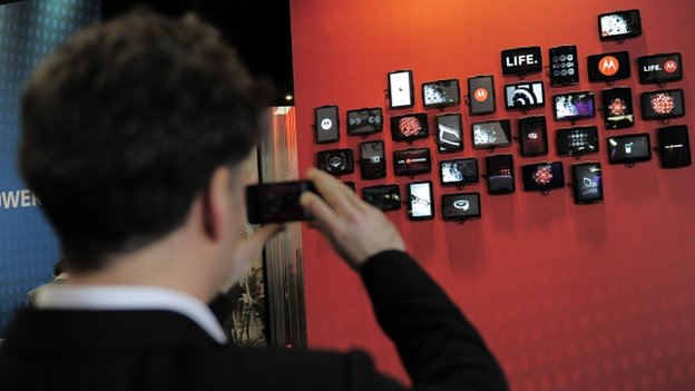 Man takes pictures with his mobile phone at the Motorola stand of the Mobile World Congress in Barcelona