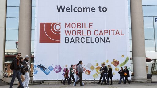 People walk by the main entrance of the Mobile World Congress in Barcelona