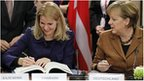 Danish PM Helle Thorning-Schmidt (left) signs fiscal treaty, with Germany's Chancellor Angela Merkel