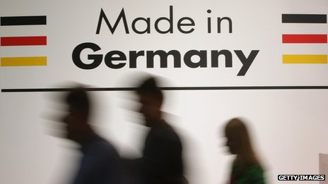 People walk past a sign saying 'made in Germany'