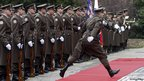A member of the Croatian honour guards jumps over the red carpet before the arrival ceremony for Austria's President Heinz Fischer