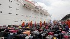 Passengers from the Costa Allegra cruise ship look for their baggage upon their arrival at Victoria&#039;s harbour, Seychelles