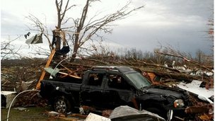 A car lies amid wreckage after a storm hit near New Pekin, Indiana