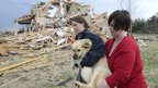 Lisa Copeland, right, and Kacie Rose carry a dog to a safe place before a second round of storms approaches Ooltewah, Tennessee 2 March 2012
