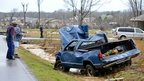 People look at a car that blew off the road during a tornado in Harvest, Alabama 2 March 2012