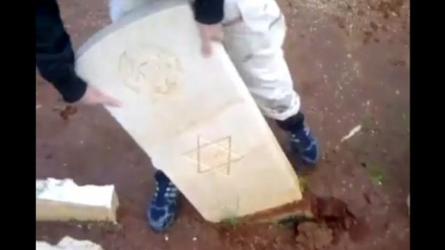 Headstone being vandalised at the Benghazi War Cemetery
