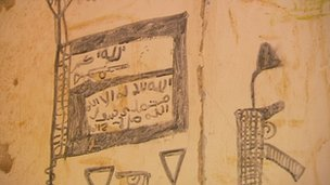 Al-Shabab flag and Jihadist writings in charcoal on the wall