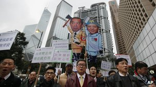 Traders and stock brokers protest against longer trading hours in Hong Kong's financial district on February 28