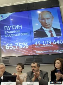 Members of the Central Election Commission applaud as Russian Prime Minister Vladimir Putin (pictured on screen) is announced winner of the presidential elections according to preliminary election results in Moscow