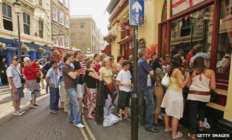 Fans crowd around a pub to watch an England match