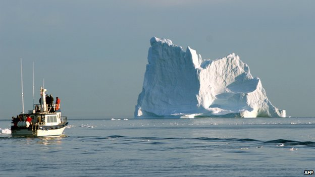 A boat cruises near iceberg off the coast of Greenland