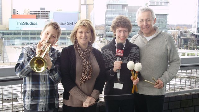 School Reporter Sam with his family at MediaCityUK ready with their instruments for the Music Nation event.