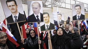 Pro-regime supporters in Damascus with posters of President Assad and Russian President-elect Vladimir Putin