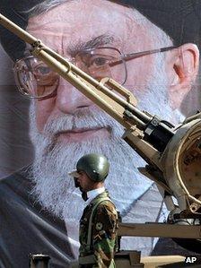 Um soldado do exército iraniano saúda na frente de um retrato do líder supremo, o aiatolá Ali Khamenei (2005)