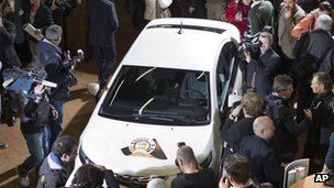 Cameramen and journalists crowd around a car at the motor show
