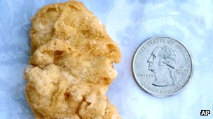 Chicken McNugget said to resemble President George Washington beside a coin showing the head of Washington, in a file photo from 21 February 2012