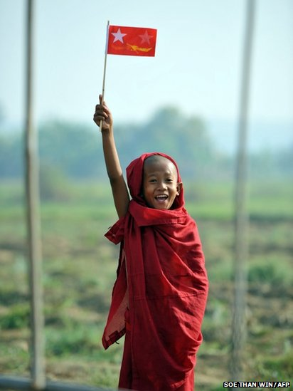 A Buddhist novice waves a National League for Democracy flag
