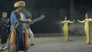 Three men confront a woman wearing yellow