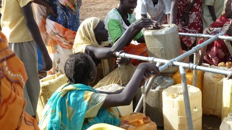 Women fill bottles at a refugee camp but water is scarce