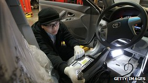 A worker checking brake pedals in a Toyota Camry car