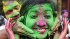 "A student of Rabindra Bharati University applies coloured powder to a fellow student""s face as they celebrate Holi."