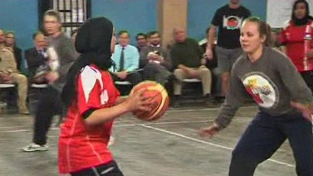 Afghan women playing basketball with a team from the International Security Assistance Force and the US embassy