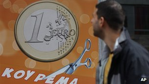"A pedestrian looks at a sign in a shop in Athens reading ""One euro, price haircut"""