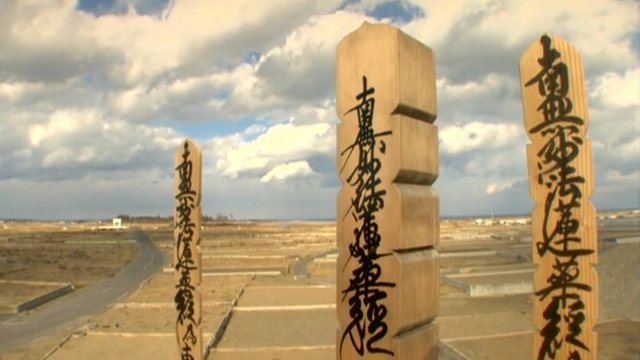 Empty plains that were once Japan&#039;s Yuriage - with wooden stakes in the foreground.