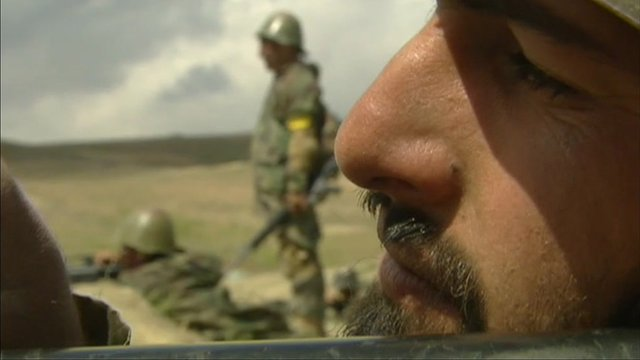 Soldier in Afghanistan looks down the barrel of a gun.