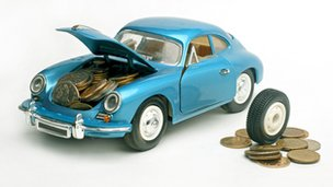 A blue toy car with money in the body