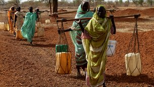 Refugees carry water