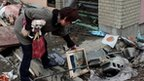 Woman sifting through rubble a few days after the earthquake hit