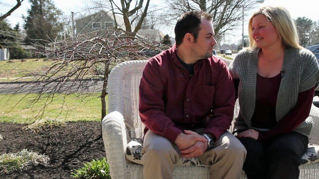Young Levittown couple sitting on bench