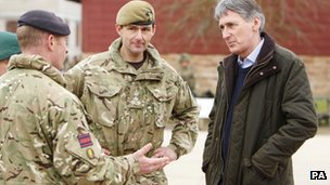 Defence Secretary Philip Hammond and Brigadier Doug Chalmers speak with military personnel during a visit to Copehill Down, a Ministry of Defence training area in Wiltshire