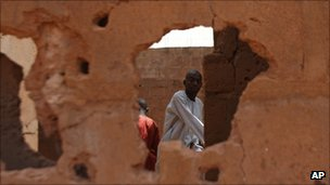 A man is seen through a hole punched out by gunfire in an abandoned home that took heavy fire during a military operation to free two hostages in Sokoto, Nigeria