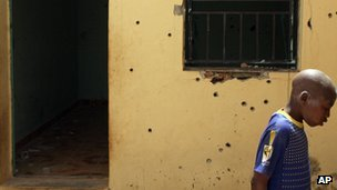 A boy walks past bullet holes in the building where the rescue bid took place