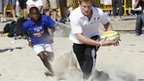 Prince Harry and young boy playing rugby.