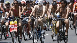 Hundreds of nude and semi-nude cyclists demanding that authorities stop the hostilities bicyclists face from motorists, pedal through a main avenue in Lima, Peru, Saturday March 10, 2012