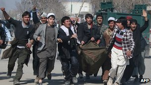 Afghan demonstrators carry a counded man as they protest against Koran desecration in Kunduz, february 25