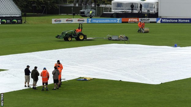 The Dunedin pitch is covered as rain falls