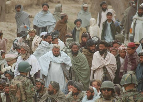 Afghan men gather in the area of the Kandahar villages where the attacks took place, 11 March 