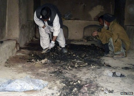 An Afghan man examines the scene of one of the attacks in Kandahar, 11 March