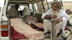 Afghan man sits next to the covered bodies of people killed in Kandahar province