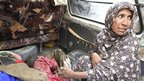 Afghan woman is interviewed next to the body of a child killed in Kandahar rampage